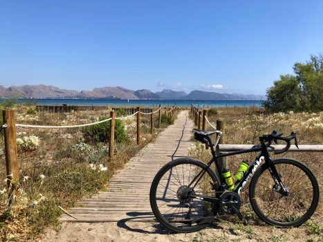 a bike on a promenade beside the sea with mountains in the background in mallorca