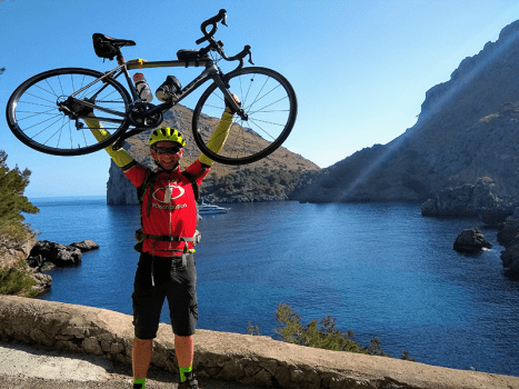 a cyclist holds up their bike beside the sea in mallorca