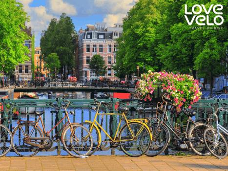 bikes lean against a bridge railing overlooking a canal in amsterdam, holland