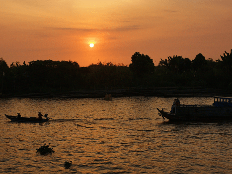 a sunset over the mekong river with boats silhouetted