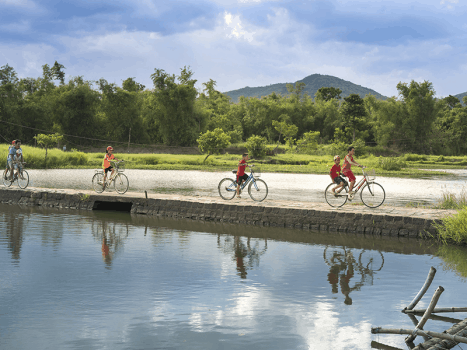vietnamese children cycle across a stone bridge over a river