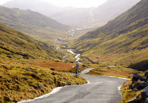 a road cyclist climbing hardknott pass in the lake district