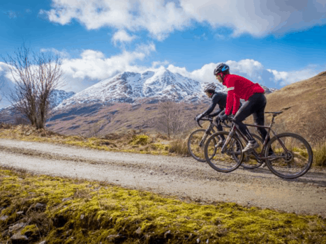 road cyclists on a road with ben lomond in the background, near lake lomond in the scottish highlands
