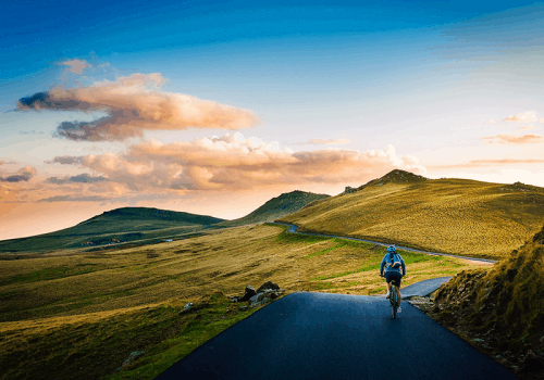 a road cyclist in the yorkshire dales between hills at sunset