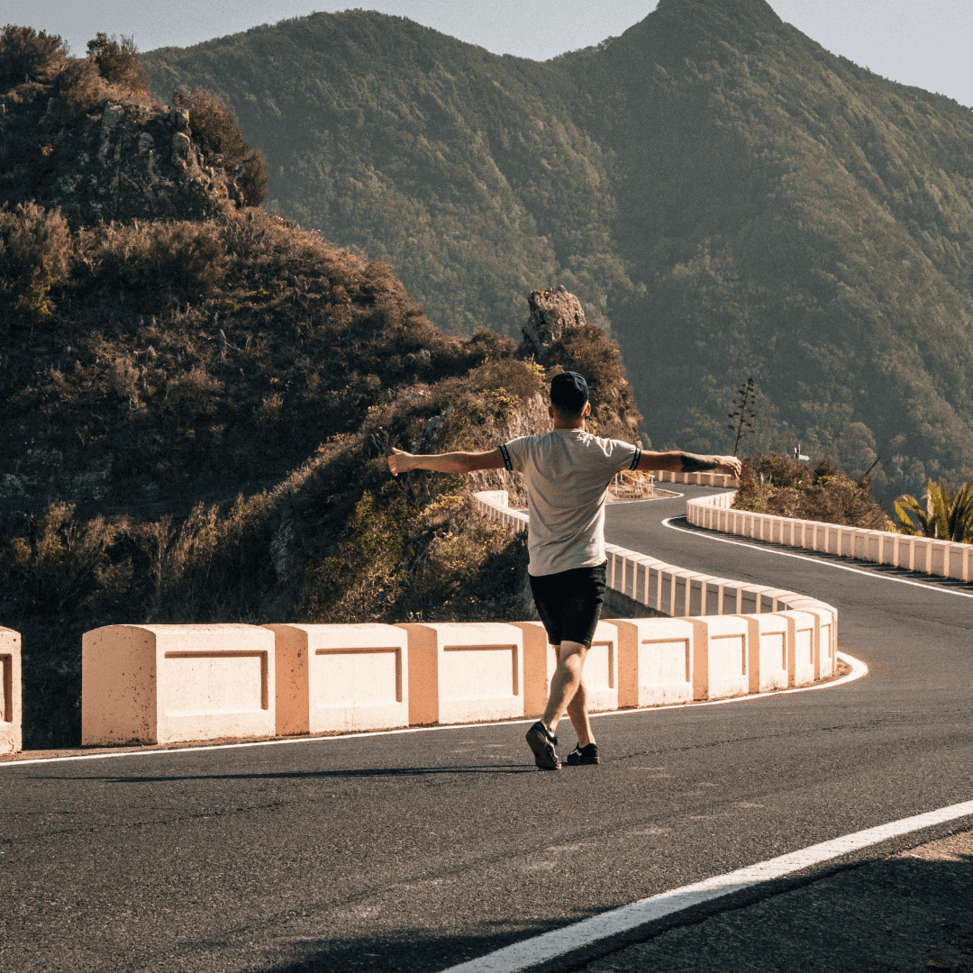 Cyclist walking along a windy road up to Mount Teide in Tenerife