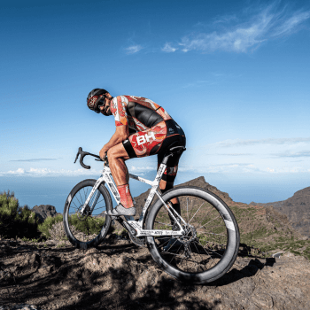 A cyclist who has stopped at the top of Mount Teide and is looking over Tenerife