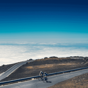 2 riders cycling in Tenerife with a view of the sky and the sea behind them
