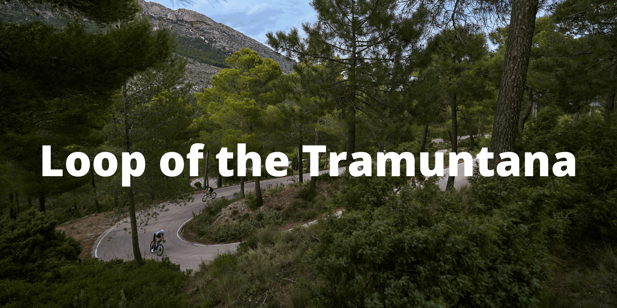 view of 2 cyclists climbing a switchback road in the Tramuntana mountains in Mallorca